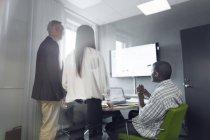 Колеги обговоренні праці на екрані — стокове фото