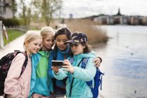 Girls taking selfie by river — Stock Photo