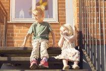 Menino e menina sentados nas escadas e olhando para longe — Fotografia de Stock