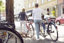 Women pushing  bikes in city — Stock Photo