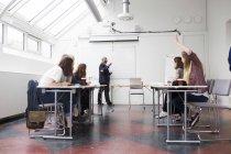 Studenten sitzen auf Vortrag mit Lehrer im Klassenzimmer — Stockfoto