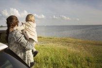 Mutter hält Sohn nahe Autotür — Stockfoto