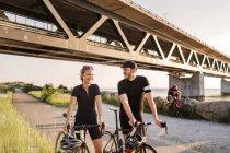 Cyclistes sous le pont à la côte — Photo de stock