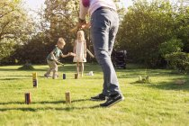 Children playing Kubb in garden with father — Stock Photo
