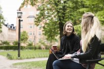 Two students sitting in schoolyard with laptop and coffee cup — Stock Photo