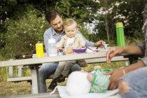 Vater mit Sohn an Picknick-Tisch sitzen — Stockfoto