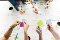 Vista superiore del colleghi utilizzando note adesive durante la riunione d'affari — Foto stock