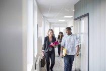 Colleagues walking through corridor — Stock Photo