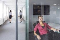 Женщина сидящая в офисе — стоковое фото