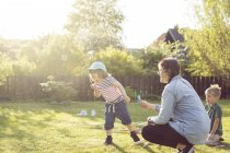 Woman and children blowing bubbles in garden — Stock Photo