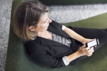 Mujer sentada en sillón acogedor - foto de stock