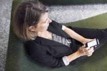 Femme assise dans le fauteuil confortable — Photo de stock