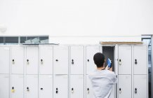 Rear view of student putting book into locker — Stock Photo