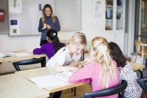 Four girls learning in classroom — Stock Photo