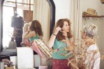 Mulher tentando brincos — Fotografia de Stock