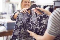 Mulher dando vestido para caixa — Fotografia de Stock