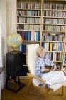 Jungen lesen Buch im Liegestuhl vor Bücherregalen im Wohngebäude — Stockfoto