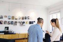Compañeros de trabajo mirando el teléfono móvil en la oficina - foto de stock