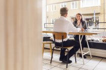Senior man and mature woman working in cafe — Stock Photo