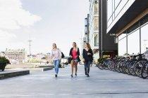 Three women walking together on street — Stock Photo