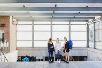 Drei junge Frauen, die über eine Treppe am Bahnhof stehen — Stockfoto