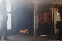 Two men inserting pork sausages into smokehouse — Stock Photo