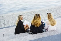 Three young women sitting on steps by river — Stock Photo