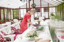 Frau Einstellung Tisch im Wintergarten — Stockfoto