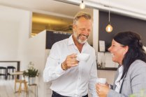 Senior man and mature woman laughing in cafe — Stock Photo