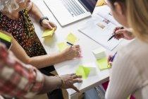 Colleghe scrivendo su foglietti adesivi durante la riunione — Foto stock