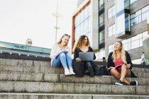 Три молодые женщины с ноутбуком, сидя на шагах — стоковое фото