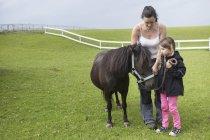 Мать и дочь (4-5), стоя с пони — стоковое фото