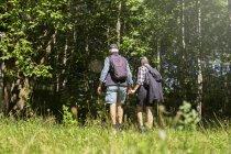 Homem e mulher caminhando no prado — Fotografia de Stock
