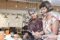 Two women using digital tablet in cafe — Stock Photo