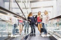 Three young women on escalator — Stock Photo