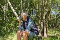 Человек пьет из чаши в лесу — стоковое фото