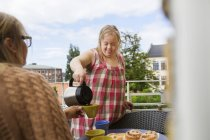 Daughter with down syndrome pouring coffee for mother on balcony — Stock Photo