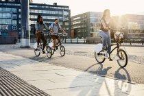 Три человека на велосипеде в городе — стоковое фото