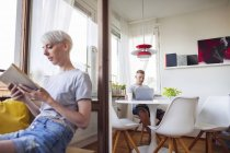 Woman reading book on balcony, man using laptop in dining room — Stock Photo