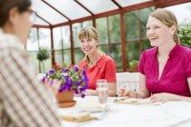 Personen im Gespräch am Tisch im Wintergarten — Stockfoto