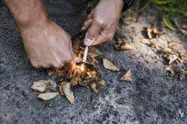 Homem acendendo fogo acampamento no chão — Fotografia de Stock