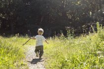 Boy (2-3) running on footpath against trees — Stock Photo