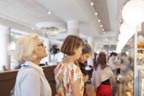 Drei Frauen, die Wahl Dessert im café — Stockfoto