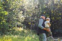 Людина холдингу онук (2-3) у денний час ліс — стокове фото
