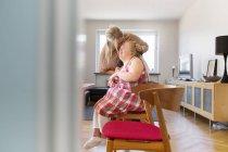 Mother kissing daughter while brushing her hair — Stockfoto