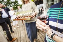 Woman holding glass of red wine at garden party — Stock Photo