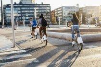 Троє людей, їзда на велосипеді по міській вулиці — стокове фото