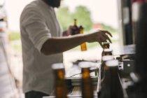 Section médiane d'ouvrier de brasserie préparation des bouteilles de bière — Photo de stock