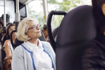 Senior woman sitting in bus — Stock Photo