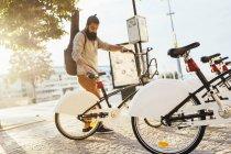 Человек принимает напрокат велосипед у стойки на станции — стоковое фото